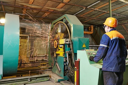 setup operator: industrial worker making metal reinforcement carcass for concrete tube pipe