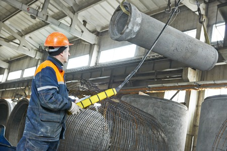 operative: worker hoisting concrete pipe tube at production workshop plant