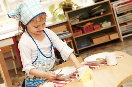playcentre: little girl serving foor breakfast at kindergarten