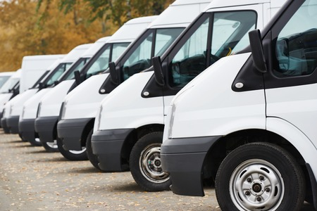 commercial delivery vans in row at parking place of transporting carrier shipping service company Stock Photo