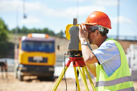 tacheometer: Portrait of builder worker with theodolite transit equipment at construction site outdoors during surveyor work