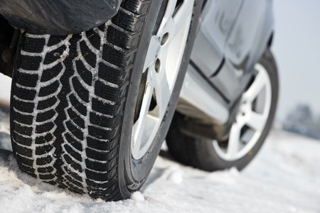 tire fitting: Car with winter tyres installed on light alloy wheels in snowy outdoors road Stock Photo
