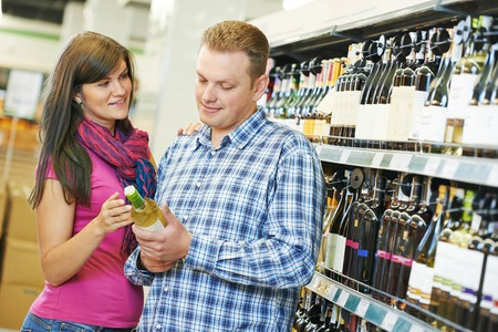 Young family couple choosing bottle а wine in supermarket during weekly shopping photo
