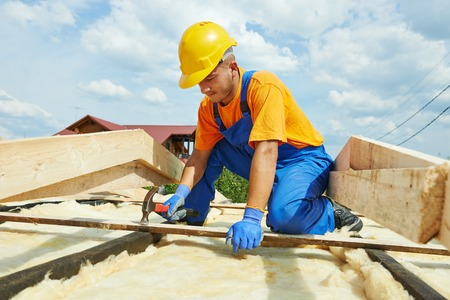 roofer: construction roofer carpenter worker hammering wood board with hammer and nail on roof installation work Stock Photo