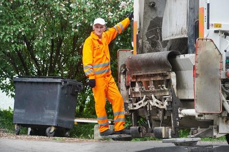 cesto basura: Trabajador de reciclaje de basura de residuos camión recolector de carga y el compartimiento de basura Foto de archivo