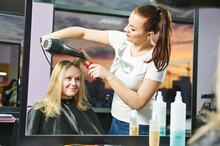 Female hairdresser drying hair with blow dryer of woman client at beauty parlour after highlighting photo