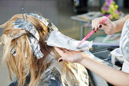 hairtician: Highlight. Coloring woman client hair in beauty parlour hairdressing salon