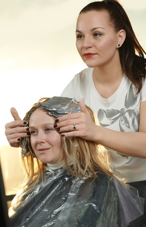 Highlight. Hairdresser woman making highlighting coloring of female client hair in beauty parlour hairdressing salon photo
