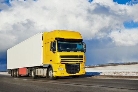 express lane: Yellow lorry cargo truck with trailer driving on highway road delivering goods
