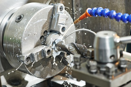 Close up machining tool drill during metal cutting process boring a hole Stock Photo