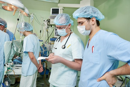 cardiosurgery: anaesthesiologist doctors in uniform preparing narcosis anaesthesia during heart transplantation operation at cardiac surgery clinic Stock Photo