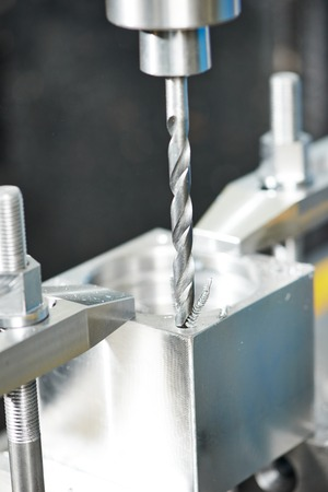 affixment: Close up machining tool drill during metal cutting process boring a hole Stock Photo