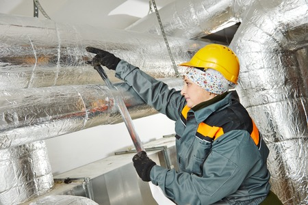 foil: Thermal insulation. Female insulation worker isolating industrial pipe with glass wool and foil Stock Photo
