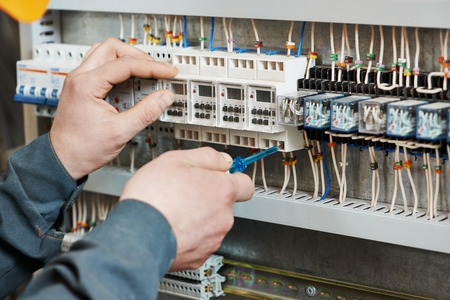 Hands of electrician with screwdriver tighten up switching electric actuator equipment in fuse box Stok Fotoğraf