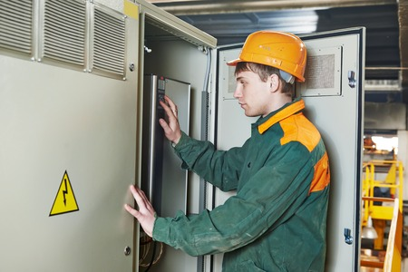 fuse box: Young adult electrician builder engineer switching actuator equipment in distribution fuse box