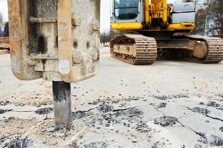 roadwork: Excavator breaking street asphalt with hydrohammer drill at repairing roadwork Stock Photo