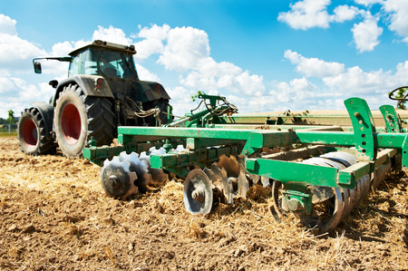 plough land: Ploughing heavy tractor during cultivation agriculture works at field with plough
