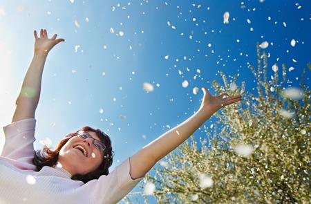 optimismo: Mujer joven feliz que levanta las manos en alto en la floración de primavera al aire libre