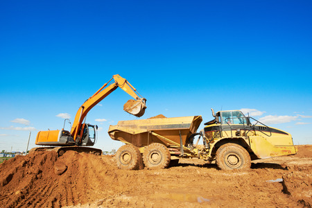 wheel loader excavator machine loading dumper truck at sand quarry photo