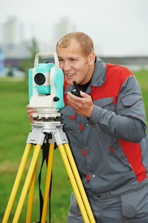 tachymeter: One surveyor worker working with theodolite transit equipment at spring field construction site outdoors