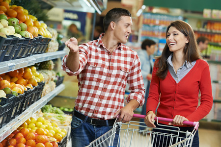 trolley: Young Family couple choosing bio food fruit in vegetable supermarket during weekly shopping Stock Photo