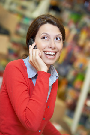 Young woman smiling and speaking on phone during shopping at supermarket store photo
