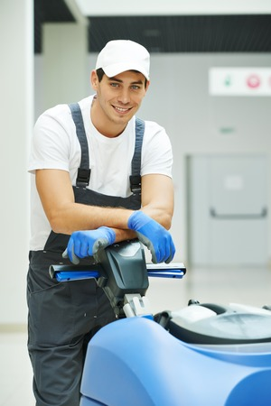 cleaner: Cleaner male man workers with mop in uniform cleaning corridor pass or hall floor of business building Stock Photo