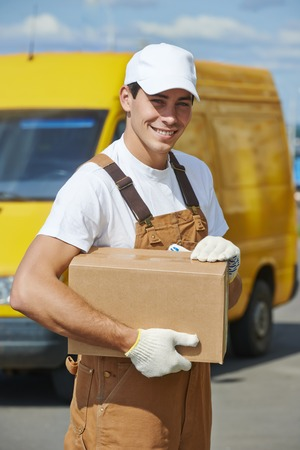 Smiling young male postal delivery courier man in front of cargo van delivering package photo