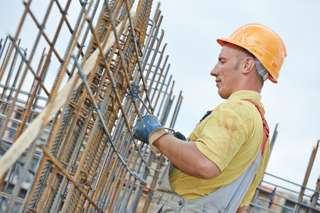 reinforcing bar: builder worker knitting metal rods bars into framework reinforcement for concrete pouring at construction site Stock Photo