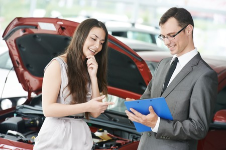 Car salesperson demonstrating new automobile to young woman photo