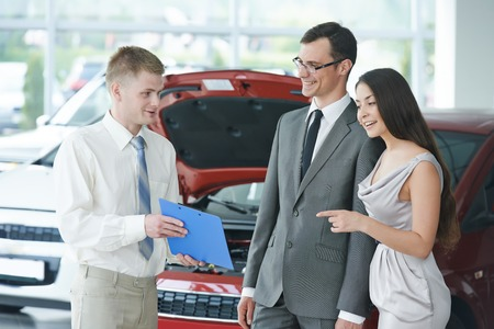 Car salesperson demonstrating rental or new automobile to young woman photo