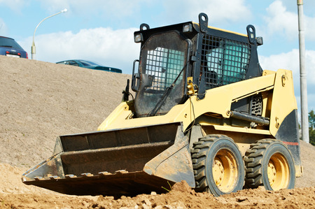 skid loader: skid steer loader moving sand soil at construction area outdoors Stock Photo