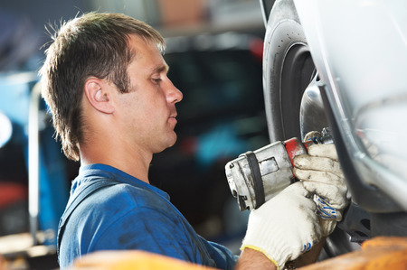 car mechanic screwing or unscrewing car wheel of lifted automobile by pneumatic wrench at repair service station Stock Photo - 27914864
