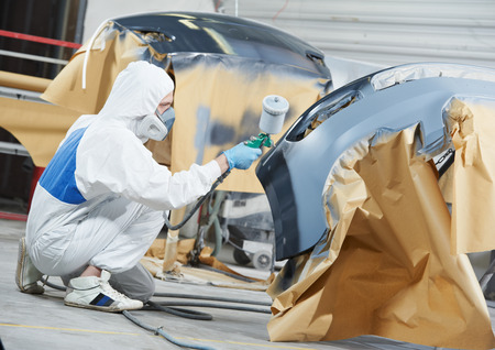 paint gun: auto mechanic worker painting car bumper at automobile repair and renew service station shop by spraing black color paint Stock Photo