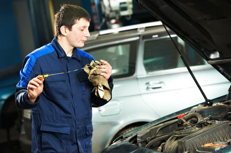 scheduled replacement: auto mechanic technician examining level during replacing and pouring motor oil into automobile engine at maintenance repair service station Stock Photo