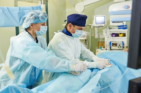 Team of vascular surgeon in uniform perform operation on a patient at cardiac surgery clinic photo