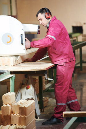 carpenter worker with circular saw machine at wood beam cross cutting at furniture manufacturing factory photo