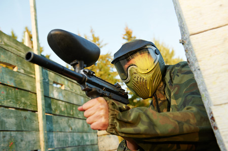 paintball: paintball player in prootective uniform and mask aiming and shoting with marker outdoors