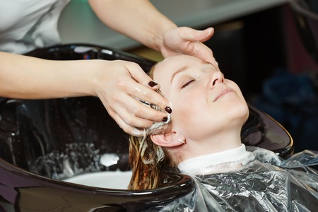 Highlight. Washing woman client hair in beauty parlour hairdressing salon photo