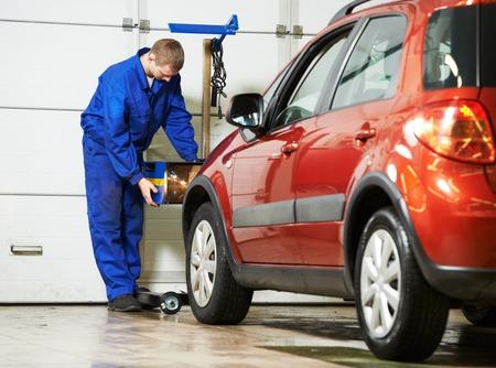 auto monteur: automonteur inspecteren koplamp lamp van de auto bij reparatie tankstation