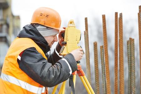 teodolito: Un trabajador del topógrafo trabaja con equipos de tránsito teodolito en el sitio de construcción de la carretera al aire libre