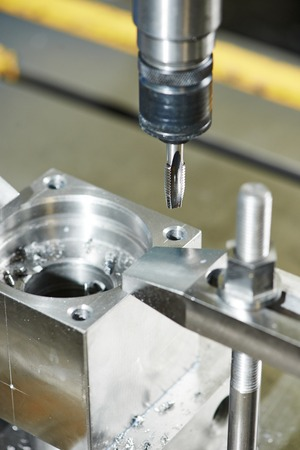 affixment: Close up machining tool thread former tap during metal cutting process