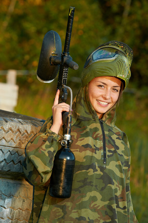 Happy paintball sport player girl in protective camouflage uniform and mask with marker gun outdoors photo
