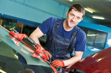 Portrait of automobile glazier repairman at windscreen or windshield of a car replacement in auto service station garage