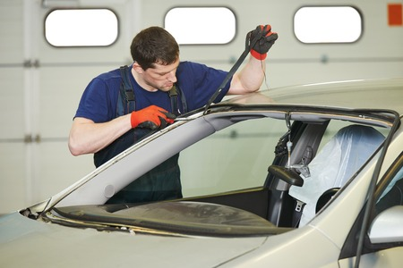 replacement: Automobile glazier worker disassembling windscreen or windshield of a car in auto service station garage before installation Stock Photo