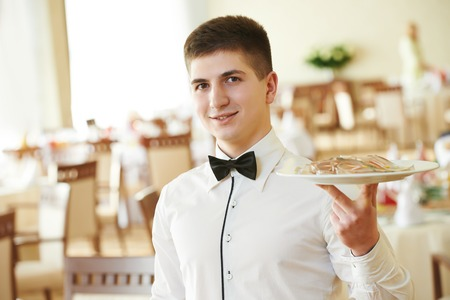 young male waiter with food on tray serving at restaurant photo