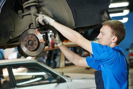 mecánico de automóviles reemplazar las zapatas de freno de rueda de coche del automóvil levantado en la estación de servicio de reparación Foto de archivo