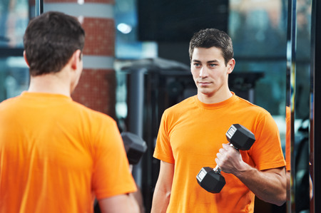 Smiling athlete man at biceps brachii muscles exercises with training dumbbells in fitness gym photo