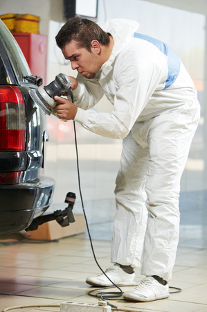 auto mechanic worker polishing car at automobile repair and renew service station shop by power buffer machine photo