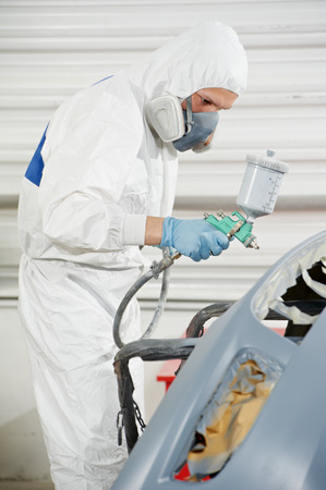 priming paint: auto mechanic worker painting car bumper at automobile repair and renew service station shop by spraing black color paint Stock Photo